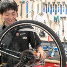 アイキャッチ画像:スポーツバイクのリアディレイラー調整をしているスタッフ
