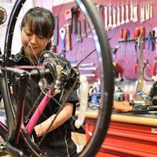 写真:女性用自転車を組み立てる女性スタッフ